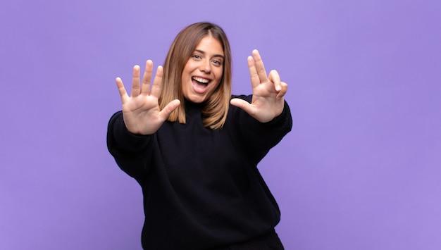 笑顔でフレンドリーに見える若いブロンドの女性、前に手を前に8番または8番を示し、カウントダウン