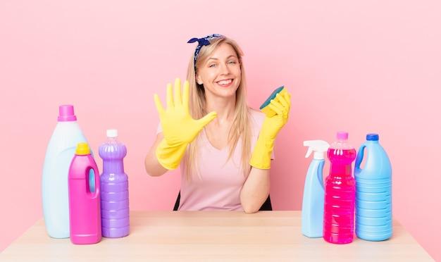 Молодая блондинка улыбается и выглядит дружелюбно, показывая номер пять. концепция домработницы