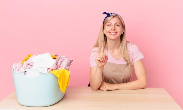 Молодая блондинка улыбается и выглядит дружелюбно, показывая номер один. концепция стирки одежды