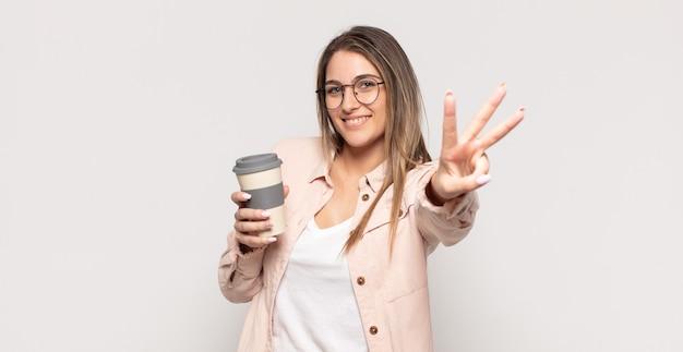 젊은 금발의 여자가 미소하고 친절한 찾고, 앞으로 손으로 3 번 또는 세 번째를 보여주는 카운트 다운