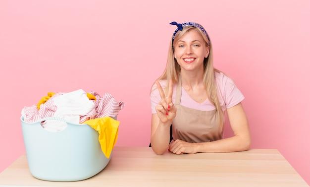 Молодая блондинка улыбается и выглядит дружелюбно, показывая номер два. концепция стирки одежды