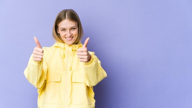 Молодая блондинка женщина улыбается и поднимает палец вверх