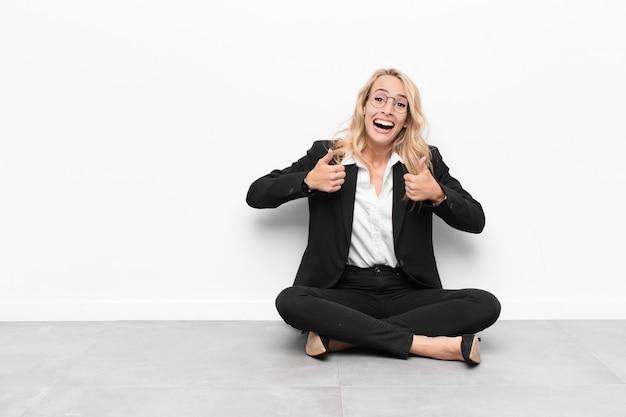 両方の親指を床に座って親指を広く見て幸せ、肯定的、自信を持って成功した笑顔の若いブロンドの女性