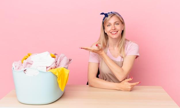 Молодая блондинка весело улыбается, чувствует себя счастливой и показывает концепцию. концепция стирки одежды