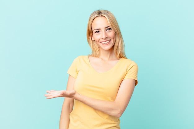 Молодая блондинка весело улыбается, чувствует себя счастливой и показывает концепцию