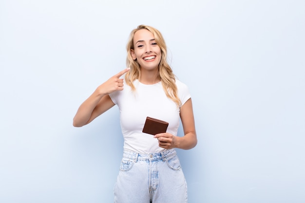 Young blonde woman smiling confidently pointing to own broad smile, positive, relaxed, satisfied attitude holding a wallet