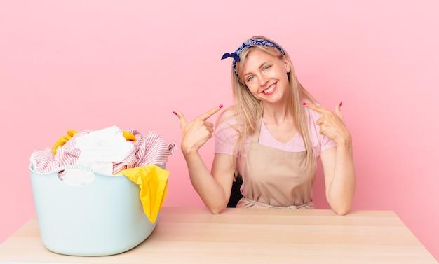 Молодая блондинка улыбается, уверенно указывая на собственную широкую улыбку. концепция стирки одежды