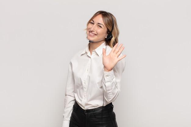 행복하고 유쾌하게 웃고, 손을 흔들며, 환영하고 인사하거나, 작별 인사를하는 젊은 금발의 여자