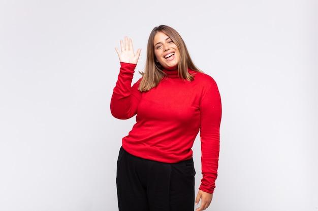 幸せで元気に笑って、手を振って、あなたを歓迎して挨拶するか、さようならを言う若いブロンドの女性