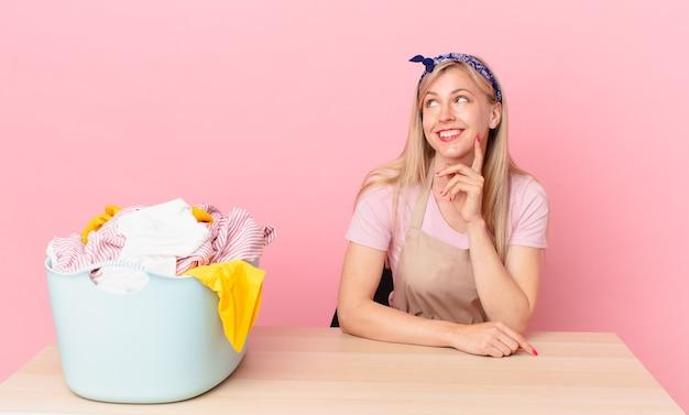 Молодая блондинка счастливо улыбается и мечтает или сомневается. концепция стирки одежды