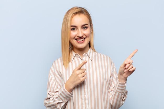 Молодая блондинка счастливо улыбается и показывает в сторону и вверх обеими руками, показывая объект в копировальном пространстве