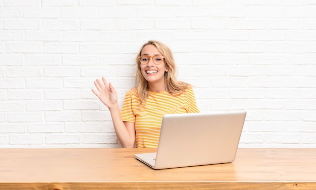 Young blonde woman smiling happily and cheerfully, waving hand, welcoming and greeting you, or saying goodbye using a laptop