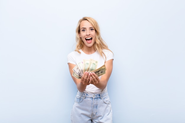 Young blonde woman smiling happily holding banknotes fan