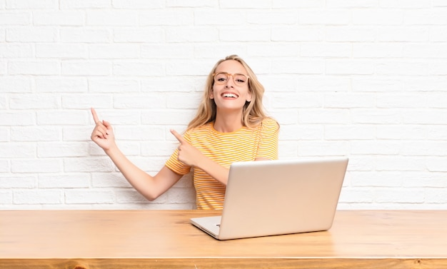 Young blonde woman smiling happily and pointing to side and upwards with both hands showing object in copy space using a laptop