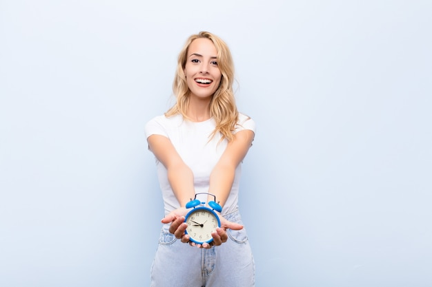 Young blonde woman smiling happily with friendly, confident, positive look, offering and showing an object or concept holding a clock