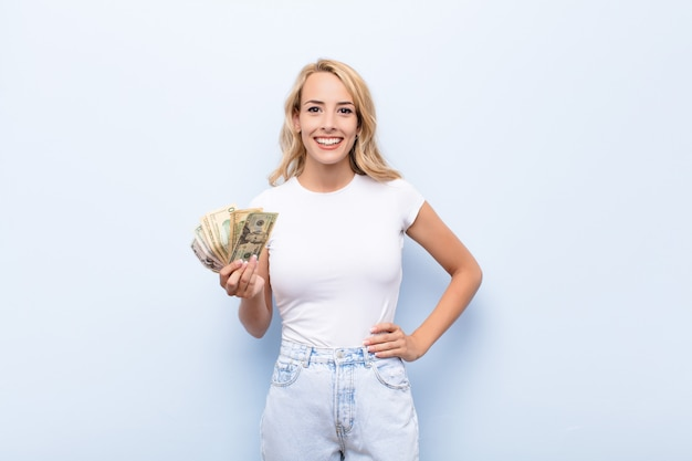 Young blonde woman smiling happily with a hand on hip and confident, positive, proud and friendly attitude with dollar banknotes