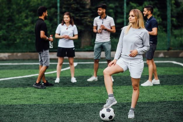 Giovane donna bionda sorridente e felice, con un pallone da calcio, entusiasta di giocare una partita