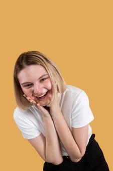 노란색에 고립 된 웃는 젊은 금발의 여자