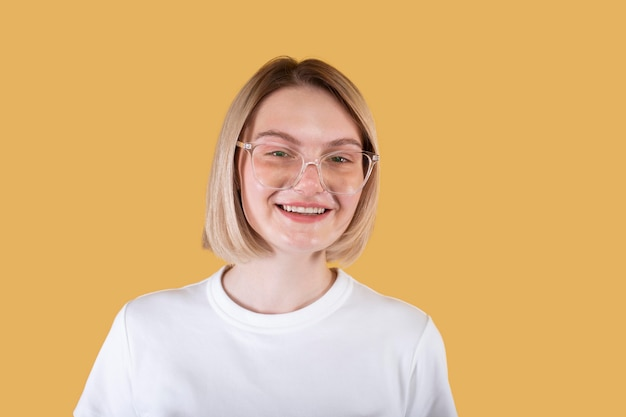 Young blonde woman smiling isolated on yellow