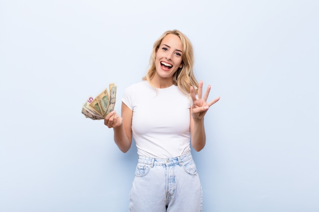 Young blonde woman smiling and looking friendly, showing number four or fourth with hand forward, counting down with dollar banknotes