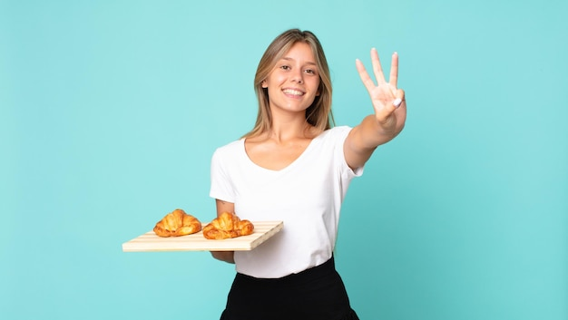 Young blonde woman smiling and looking friendly, showing number three and holding a croissant tray