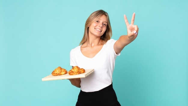 Young blonde woman smiling and looking happy, gesturing victory or peace and holding a croissant tray