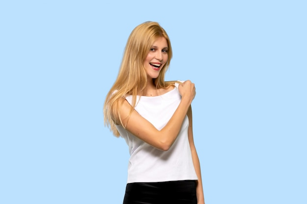 Young blonde woman smiling a lot on isolated blue background