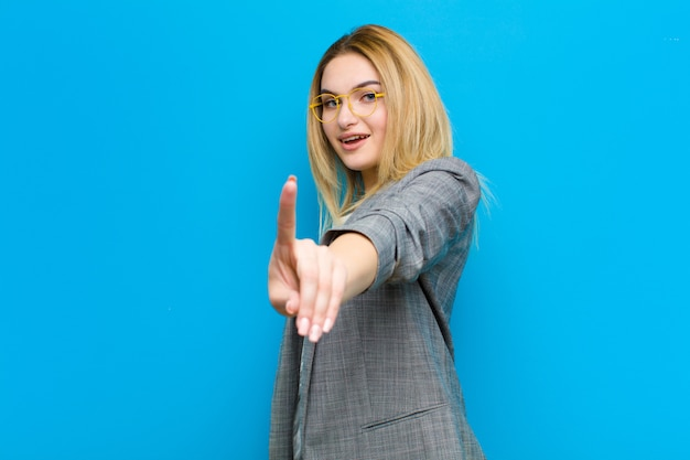 Young blonde woman smiling proudly and confidently making number one pose triumphantly, feeling like a leader on blue wall