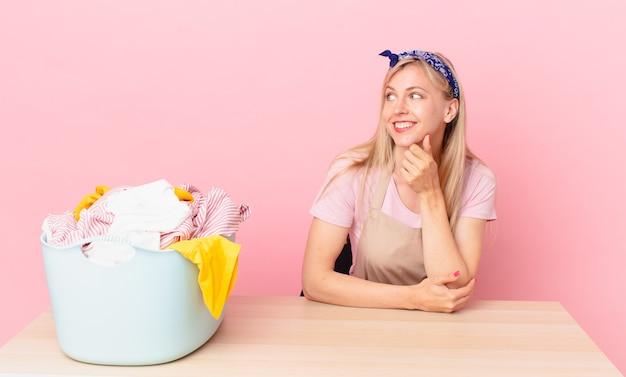 Молодая блондинка женщина улыбается с счастливым, уверенным выражением лица, положив руку на подбородок. концепция стирки одежды