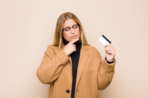 若いブロンドの女性のあごに手を幸せで自信を持って表情で笑って、疑問に思って、クレジットカードの側を見る