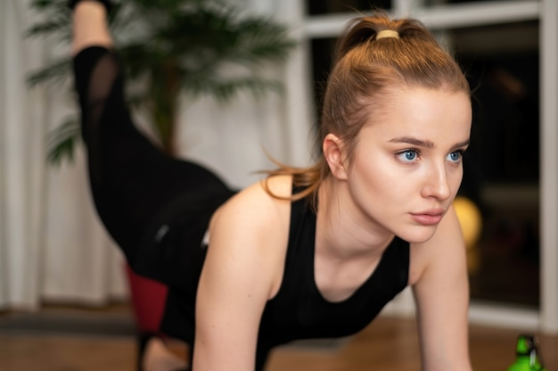 Young blonde woman in sportswear is doing exercises at home