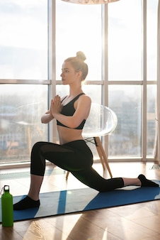 Young blonde woman in sportswear is doing yoga on a mat
