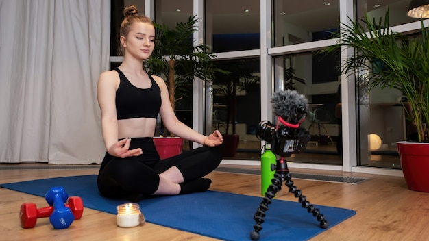 Young blonde woman in sportswear is meditating on a yoga mat looking into recording