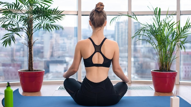Young blonde woman in sportswear is meditating on a yoga mat