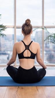 La giovane donna bionda in abiti sportivi sta meditando su una stuoia di yoga