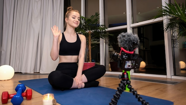 Young blonde woman in sportswear on a yoga mat waving at the recording video camera in front of her