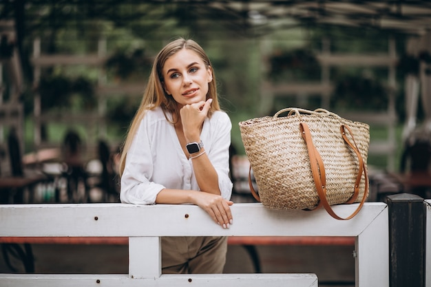 Young blonde woman standing by fence in park