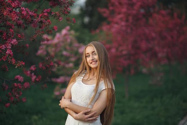 Молодая блондинка женщина, стоящая в цветущем саду. цветущая вишня. жизнерадостная женщина в белом платье улыбается и смотрит в камеру.