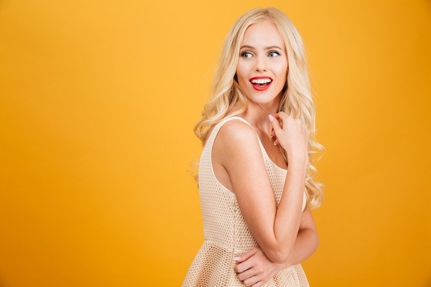 Young blonde woman standing isolated over yellow