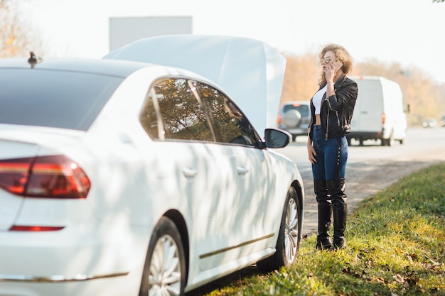 Young blonde woman standing near broken car with popped hood talking on her mobile phone while waiting for help.