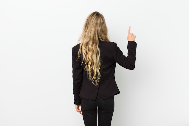 Young blonde woman standing and pointing to object, rear view over white wall
