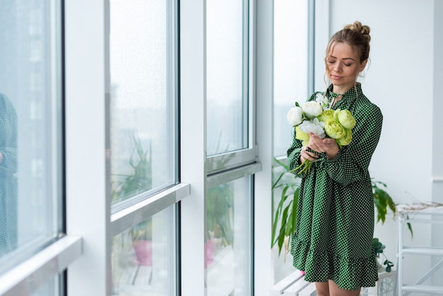 Young  blonde woman stands in the room  holds a bouquet of peonies looking on it. - image