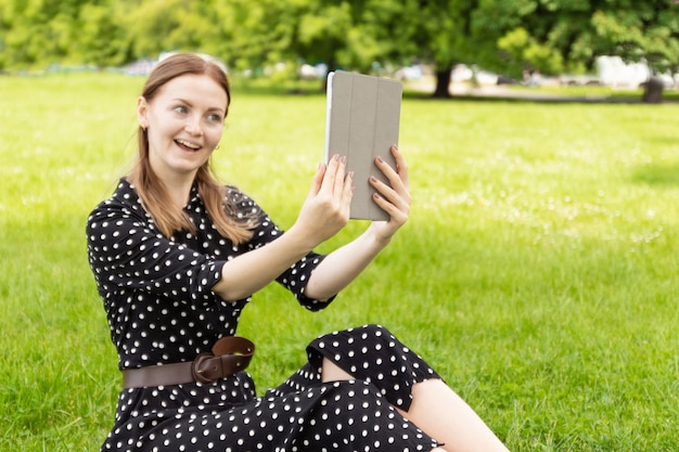 Young blonde woman in a summer dress makes selfie on a tablet while sitting on green grass in a park