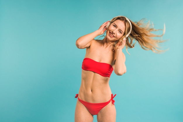 Young blonde woman in swimsuit dancing with headphones