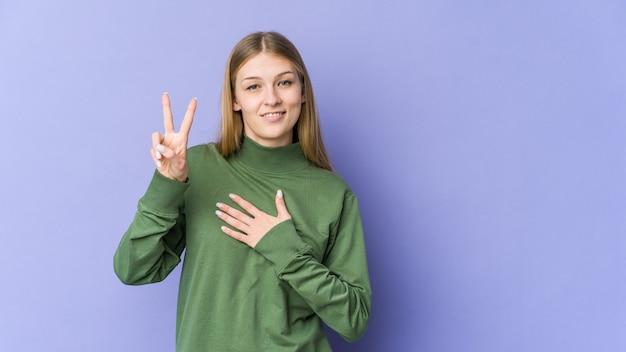 誓いを立て、胸に手を置く若いブロンドの女性。