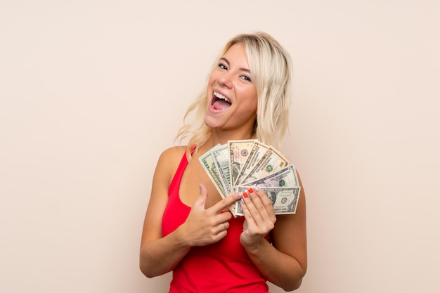 Young blonde woman taking a lot of money