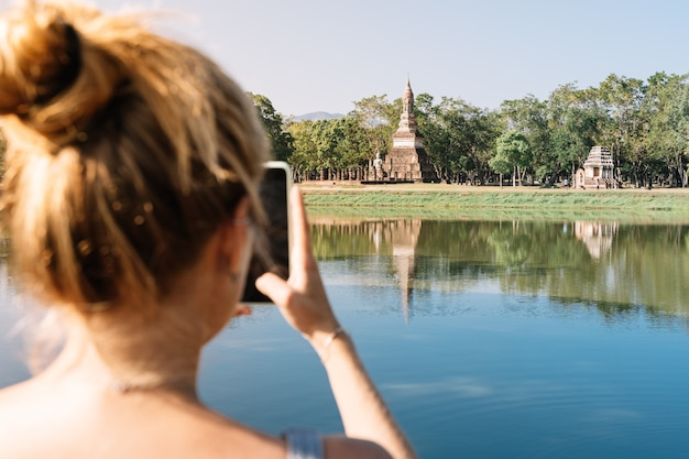 Young blonde woman taking a picture with the mobile in natural park in sukhotai, thailand