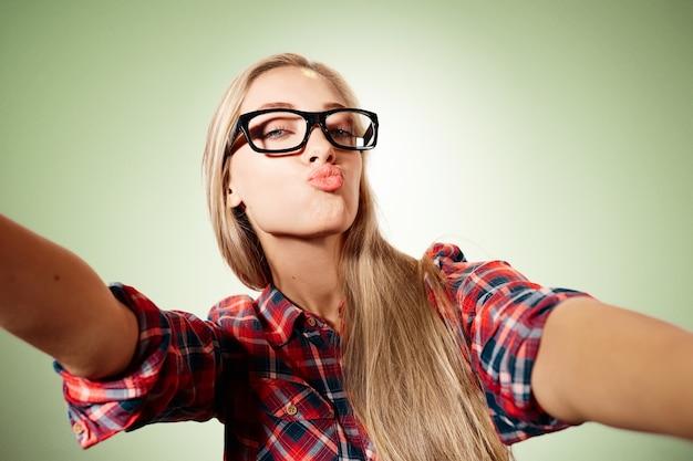 Giovane donna bionda che cattura selfie