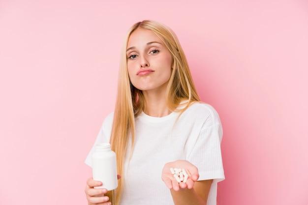 Молодая белокурая женщина принимая некоторые пилюльки изолированные на стене