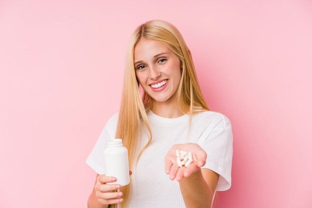 Молодая белокурая женщина принимая некоторые изолированные пилюльки